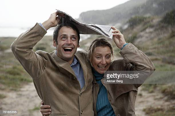 Mature couple sheltering from rain under newspaper near beach, laughing