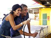 Mature couple shooting pistols at amusement park arcade