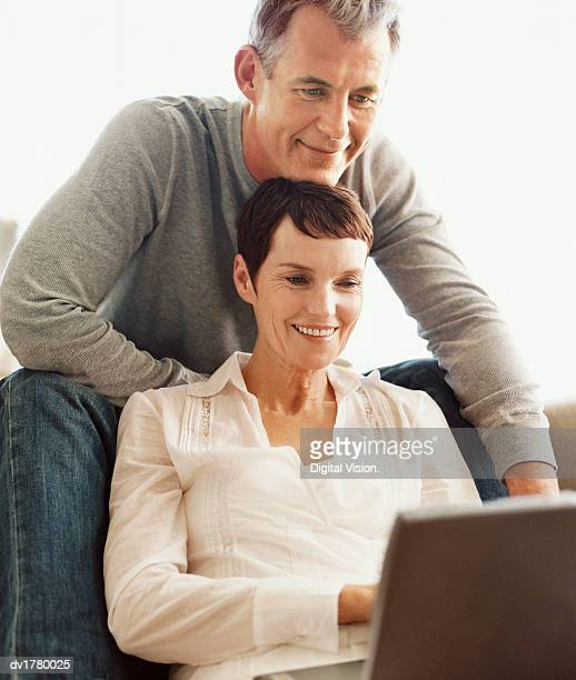 Mature Couple Sit Together Looking at a Laptop Computer