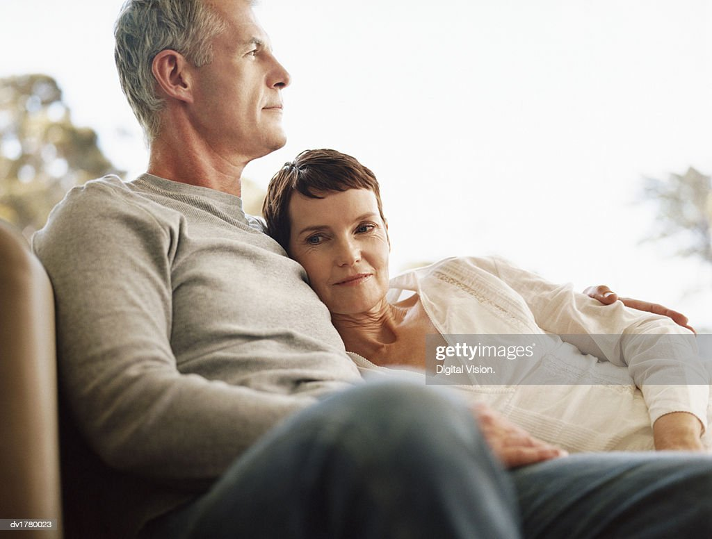 Mature Couple Sit Together on a Sofa at a Window in Front of an Overcast Sky