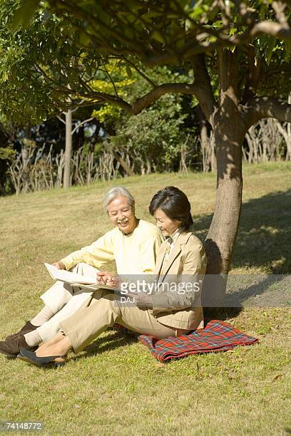 A Mature Couple Sitting by a Tree and Sketching, Full Length, High Angle View