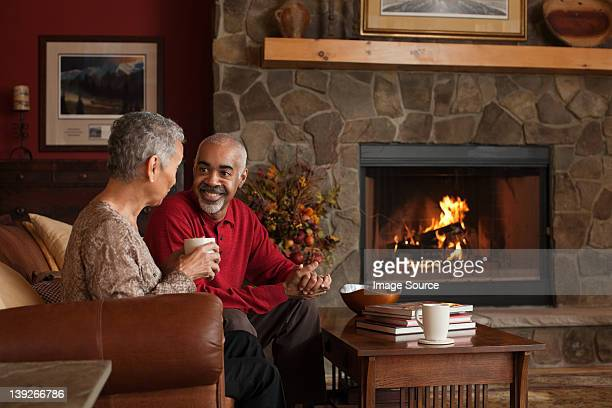Mature couple sitting by fireplace
