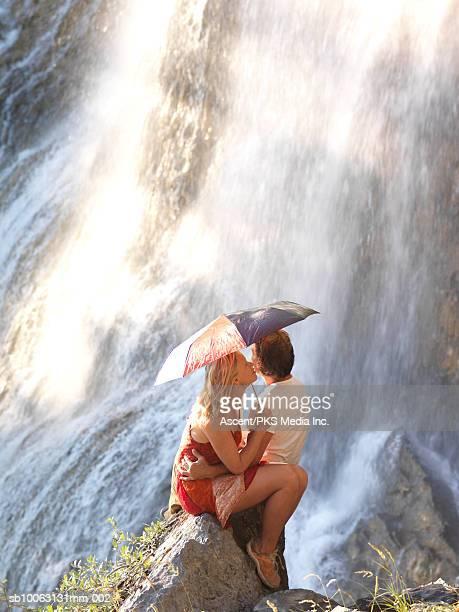 Mature couple sitting by waterfall, woman holding umbrella, kissing man