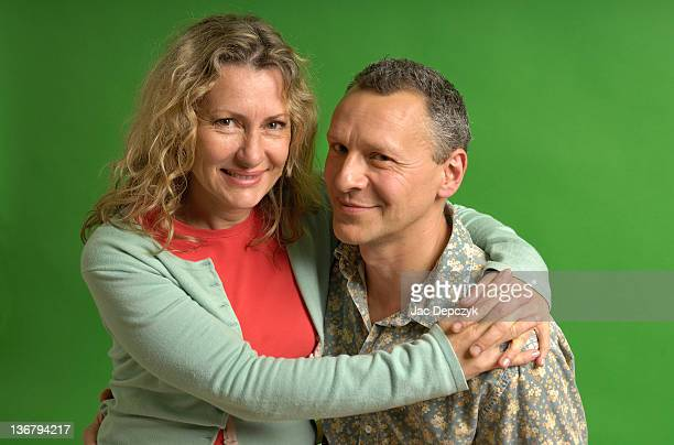 mature couple sitting, green background