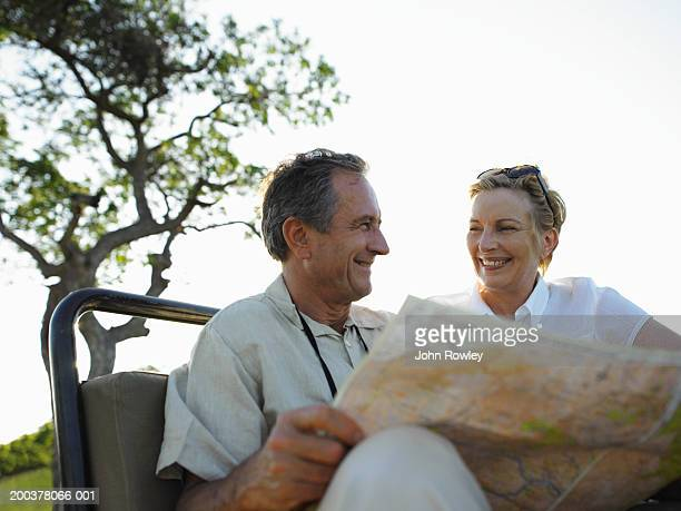 Mature couple sitting in 4x4, man holding map, smiling