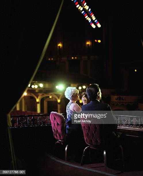 Mature couple sitting in balcony of theater, woman using opera glasses