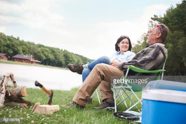 Mature couple sitting in camping chairs beside lake