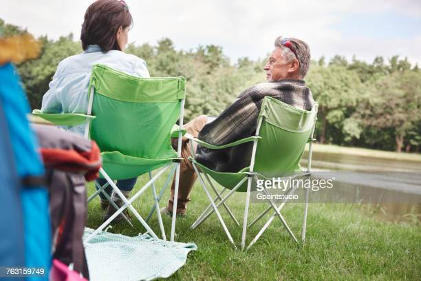 Mature couple sitting in camping chairs beside lake, rear view