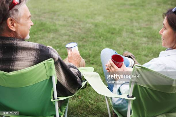 Mature couple sitting in camping chairs, holding tin cups, rear view