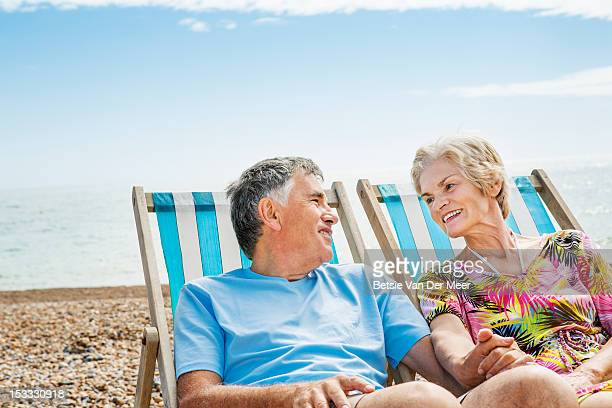 mature couple sitting in deckchairs on beach.