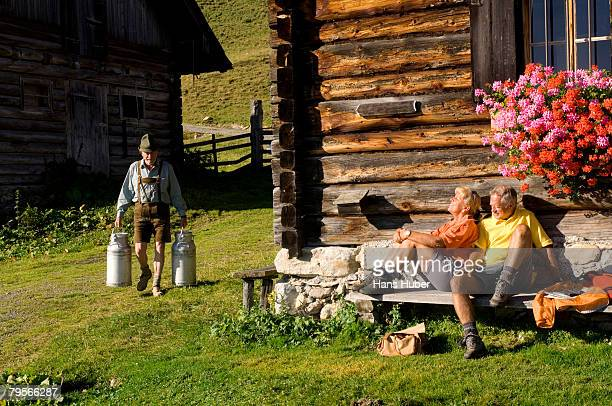 'Mature couple sitting in front of alpine hut, farmer carrying milkcans'