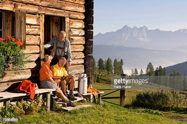'Mature couple sitting in front of alpine hut, talking to farmer'