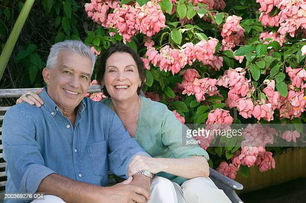 Mature couple sitting in garden chair, portrait, close-up