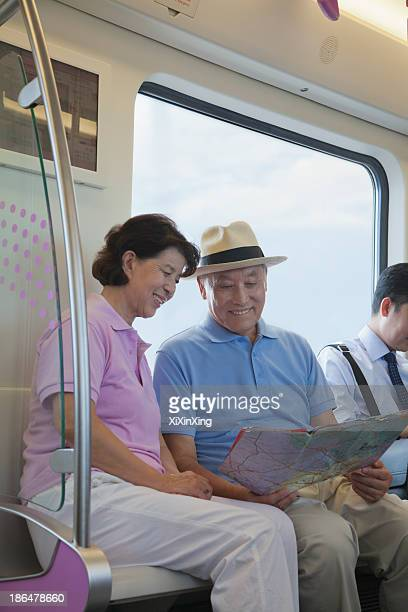 Mature couple sitting in the subway and looking at the map