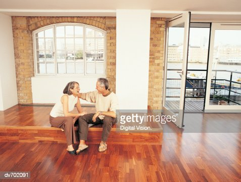 Mature Couple Sitting in Their Apartment and Laughing : Stock Photo