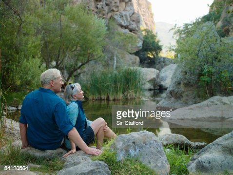 Mature couple sitting next to a canyon : Stock Photo
