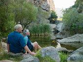 Mature couple sitting next to a canyon