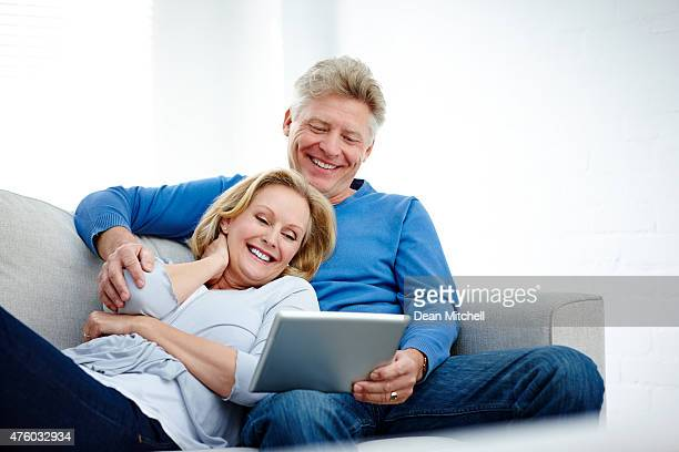 mature couple sitting on a couch using digital tablet