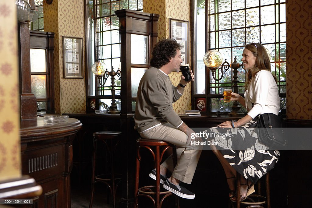 Mature couple sitting on bar stools having drinks in pub, smiling : Stock Photo
