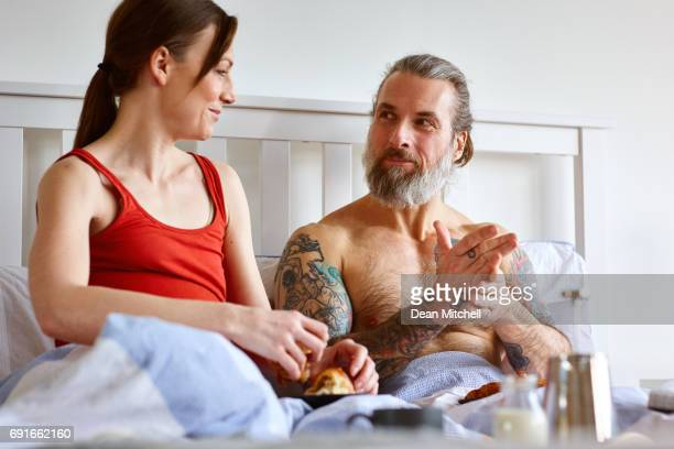 Mature couple sitting on bed in morning