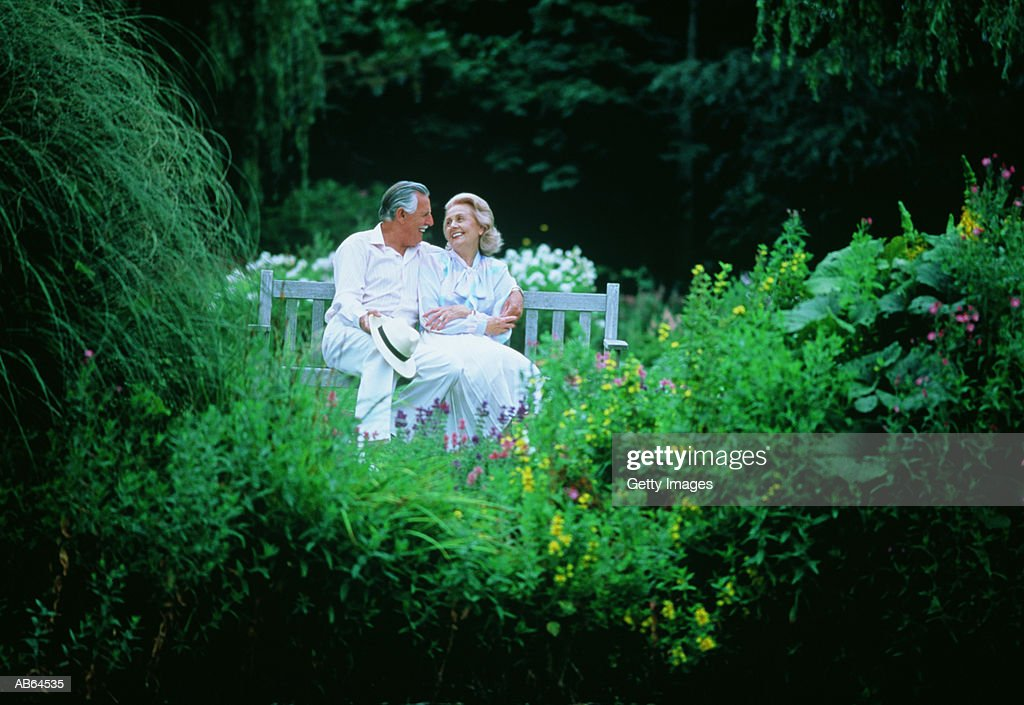 Mature couple sitting on bench in garden : ストックフォト