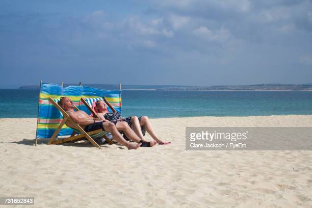 Mature Couple Sitting On Deck Chair While Relaxing At Beach Against Sky