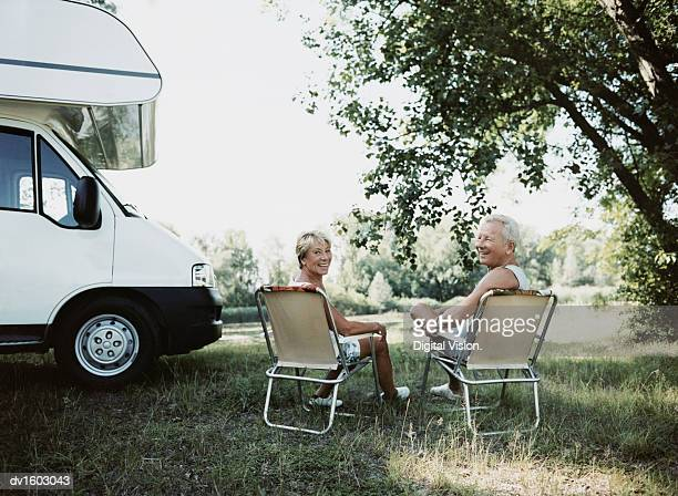 Mature Couple Sitting on Deckchairs by Their Motor Home, Looking Back at the Camera