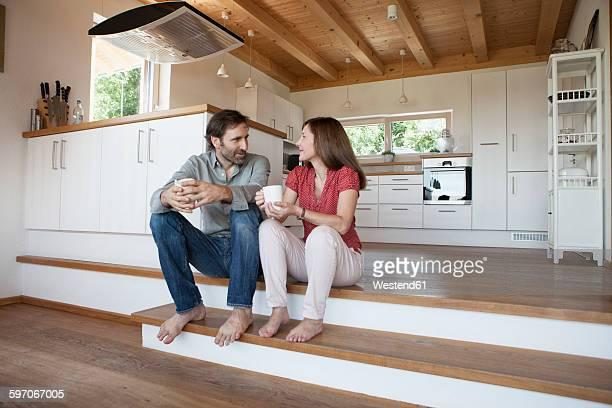 Mature couple sitting on floor, talking about future