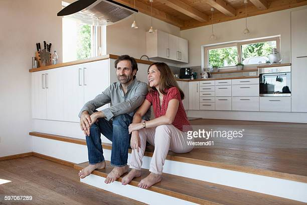 Mature couple sitting on floor, talking about future