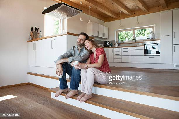 Mature couple sitting on floor, woman leaning head on mans shoulder
