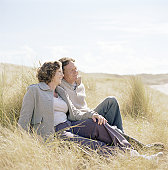 Mature couple sitting on grass, smiling