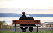 Rear view of mature couple sitting on park bench overlooking river.