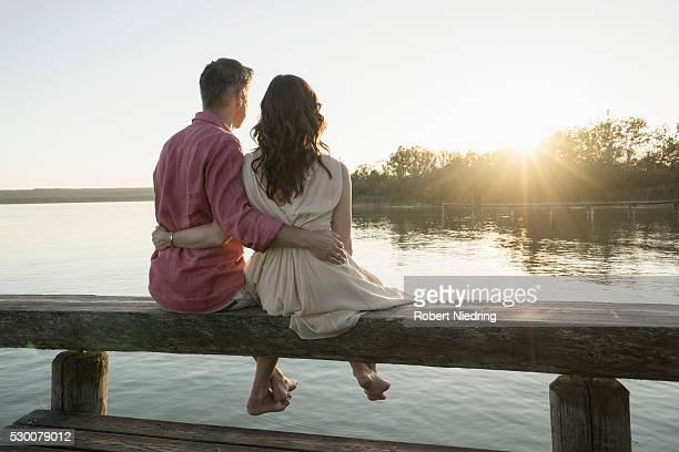 Mature couple sitting on pier looking at sunset, Bavaria, Germany