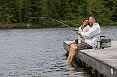 Mature couple sitting on pier, man fishing, side view