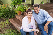 Mature couple (50s, Hispanic / Native American) at home, sitting on porch steps.