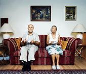 Mature couple sitting on sofa, portrait