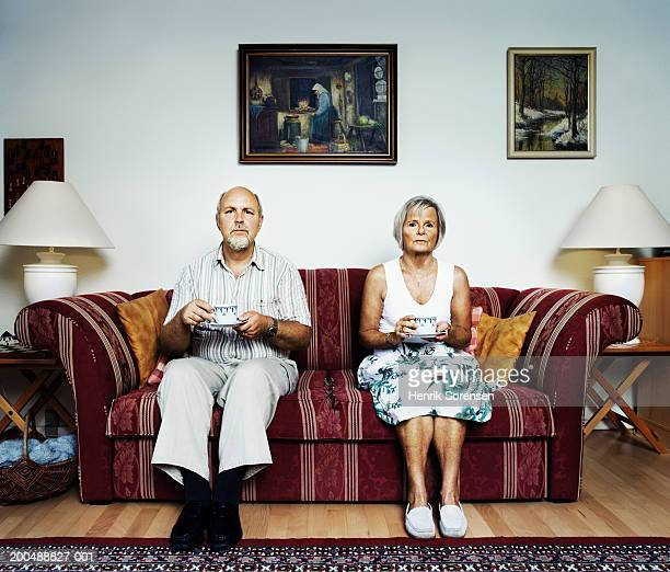 Mature couple sitting on sofa, portrait