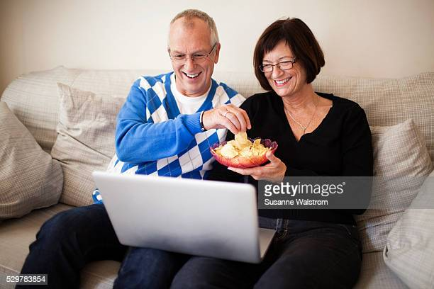 Mature couple sitting on sofa watching laptop, holding bowl of crisps