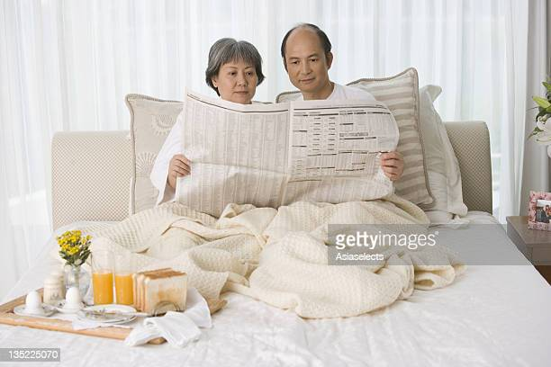 Mature couple sitting on the bed reading a newspaper