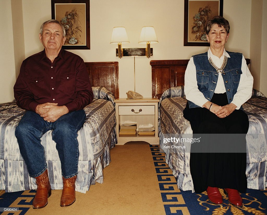 Mature couple sitting on  twin beds, portrait