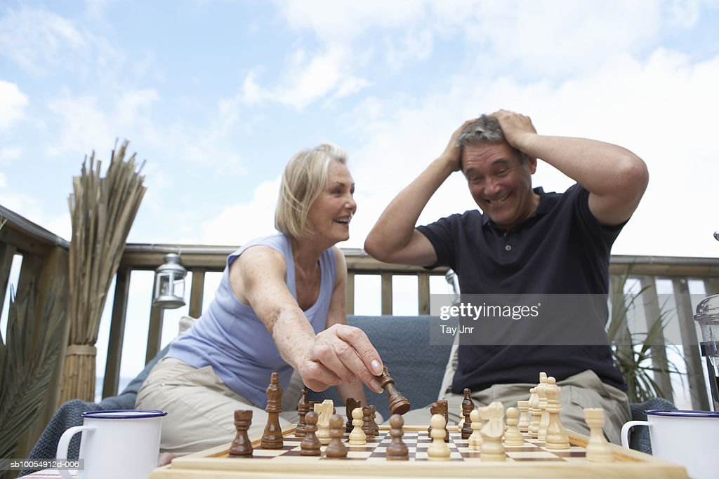 Mature couple sitting outdoors, woman moving chess piece, man reacting : Stock Photo