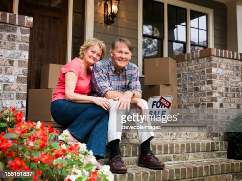 Mature Couple Sitting Outside House With For Sale Sign