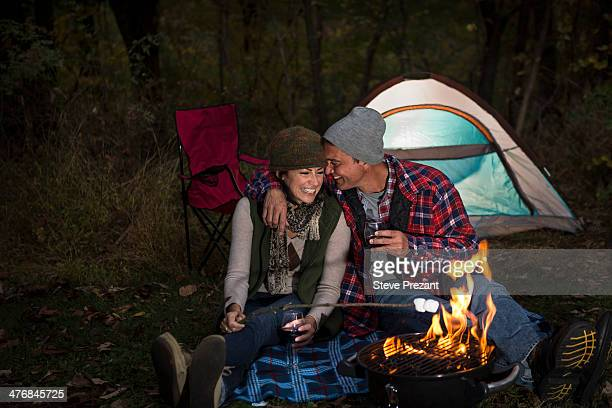 Mature couple sitting outside tent with barbecue and glass of wine