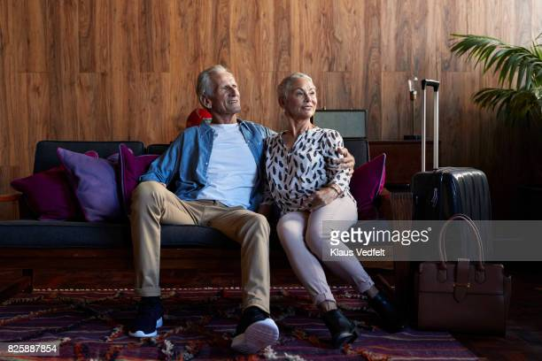 Mature couple sitting together in sofa, in modern apartment