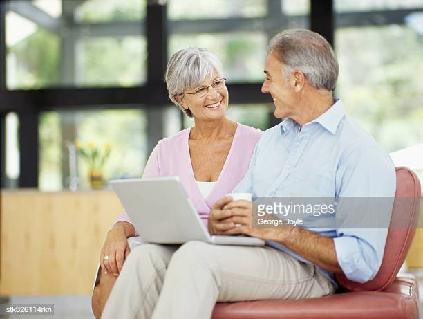 mature couple sitting together with a laptop