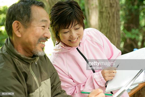 Mature couple sketching in park, close-up