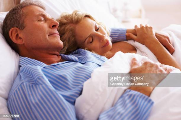 Mature couple sleeping together in bed