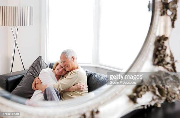 Mature couple smiling and cuddling