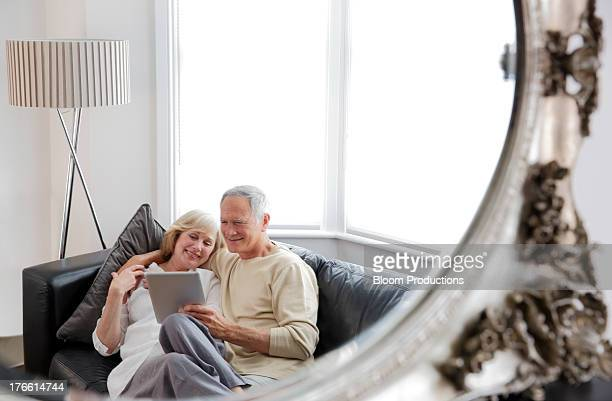 Mature couple smiling and using technology