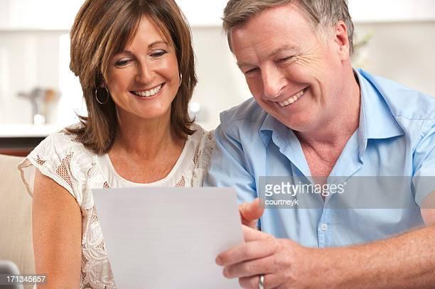 couple d'âge mûr souriant lisant un document